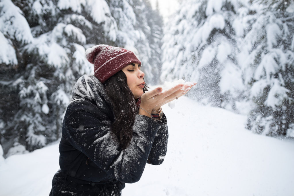 Young Beautiful Woman Blow Snow Hands In Winter Forest Girl Outdoors Walking Snowy White Park Wear Warm Clothes